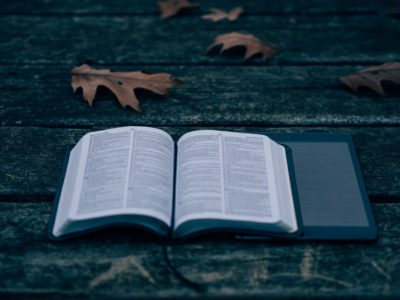 Picture of open Bible -God's Word -resting partially on top of an IPad on a gray wooden bench with few brown autumn leaves.Prophecy for Youth