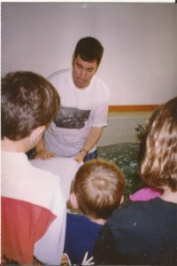 Colored photograph of a man in white T-shirt with hands on back of person in white T-shirt in baptismal pool with several children looking on.Youth ministry