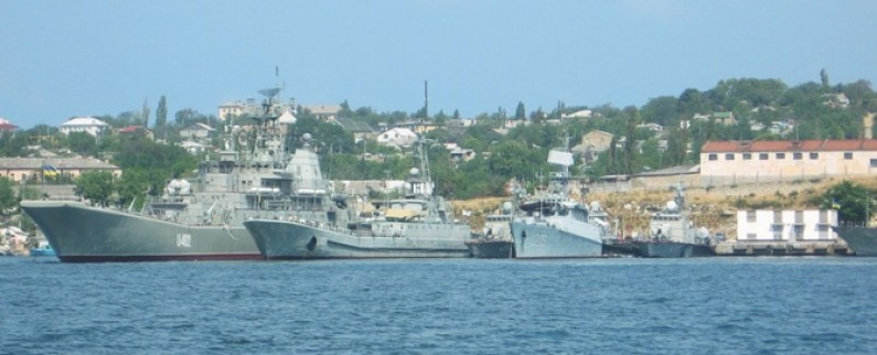 Colored photograph of Sevastopol harbour with several naval ships in foreground and buildings, houses and trees in background.