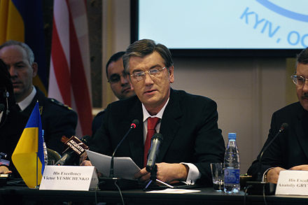 Color photograph of Viktor Yuschenko, wearing glasses, seated at a table, before a microphone, holding a sheaf of papers
