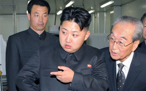 Colored photograph of Kim Jong-Un with an older man beside him and a young man behind him. He is looking and pointing at something. Is Kim Jong-Un in bible prophecy?