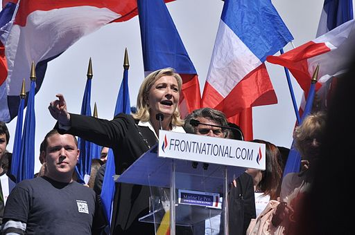 Colored photograph of Marine Le Pen on a dais at a political rally, with right arm outstretched and French flags in the background. Is France in prophetic scriptures?