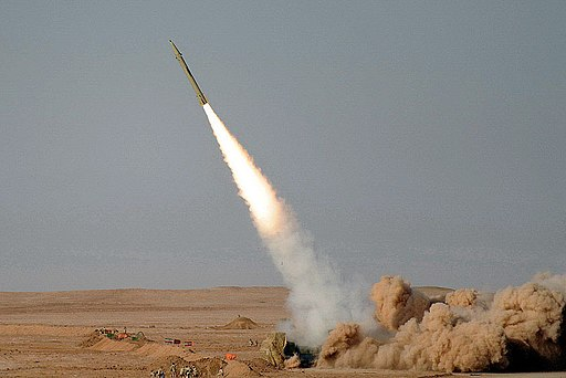 Colored photograph of Fateh-110 missile being launched, leaving behind flame, smoke and dust, in a flat, desert area