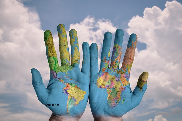 A colored photograph of a pair of hands painted blue with a map of the world painted over some of the fingers and part of the palms.The word