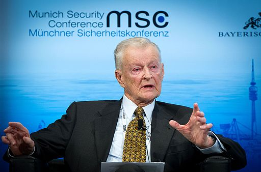 Colored photograph of Zbigniew Brzezinski,wearing a suit and tie, speaking at a Munich Security Conference. Globalist action man
