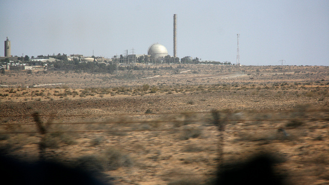 A colored photograph of Israel's alleged nuclear facility at Dimona. Looking up a desert hill towards an installation with a prominent silver dome and tall chimney. Fiery torch in the sheaves.