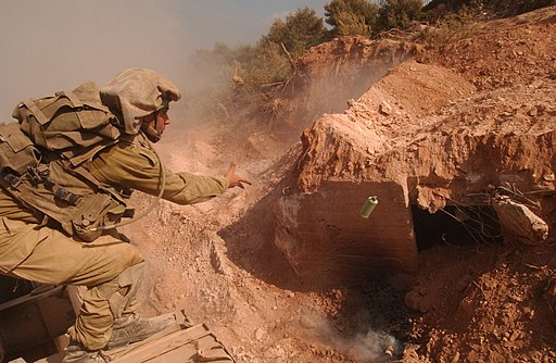 Colored photograph of a khaki-uniformed Israeli soldier throwing a grenade into a Hezbollah bunker in  clay outcrop. Fiery torch in the sheaves.