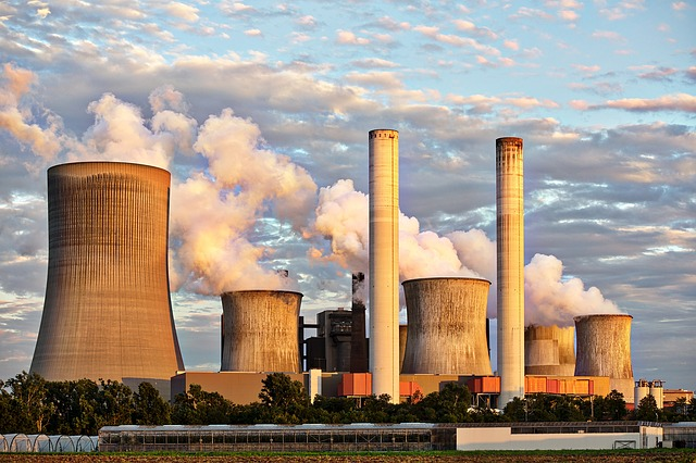 Color photograph of a power station with large cooling towers and two chimneys ; steam coming from the cooling towers that is merging with the clouds in the background. Rumors of wars.