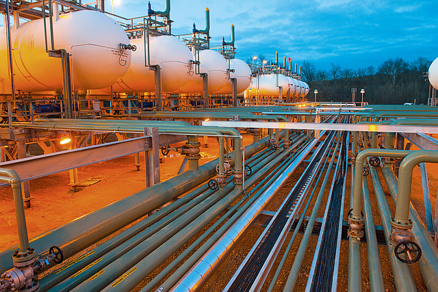 Color photograph of a large natural gas installation including storage tanks which are lit orange and many pipes reflecting the blue sky. Rumors of wars.