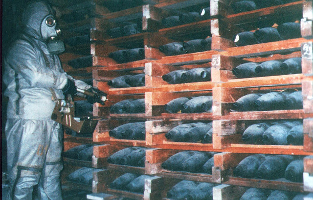 Color photograph of NBC suited soldier with a torch inspects red racks of Soviet era gas artillery shells, black and dusty. Rumors of wars.