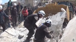 Color photograph of White Helmet members rescuing victims of a collapsed building.  Bystanders and yellow excavator in background. Rumors of wars.