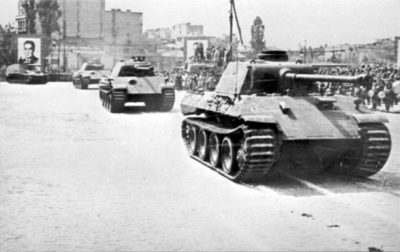 Black and white photograph of several tanks traversing a road with a picture of Romanian dictator in background. European army grows.