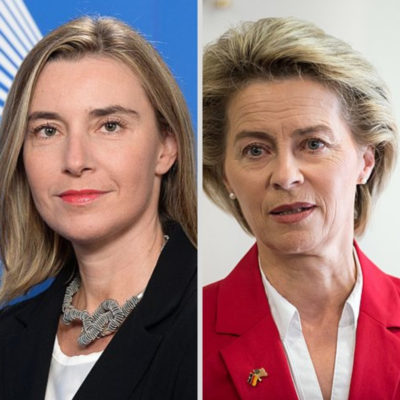 Side by side colored photographs of Mogherini with straight blond hair, dark jacket and von der Leyen, with short blond hair and red jacket. European army grows.