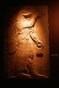 Colored photograph of stone relief showing ancient Assyrian deity. This is a humanoid with wings and eagle's head. Future Assyrian - Isaiah 10.