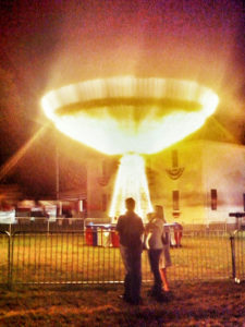 Colored photograph of flying chair amusement ride illuminated at night and resembling a gold goblet. Family in foreground observing from behind a railing. Holy Grails for Christian Youth.