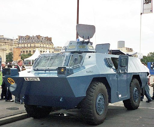 Colored photograph of a gray-blue French police four-wheeled armored car. Buildings and people in background. Waves roaring through Europe.