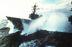 Colored photograph of warship in rough seas. Waves roaring through Europe.