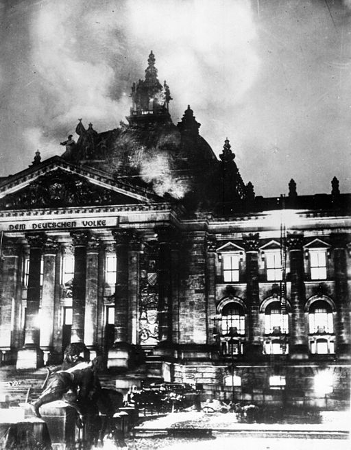 Black and white photograph of a large building aflame, illuminated from within. Stepping on Ten Toes.