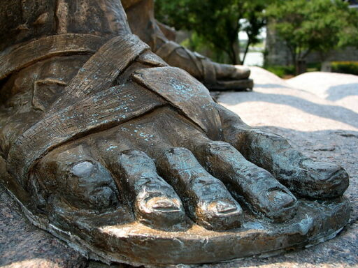 Colored photograph of the feet of a bronze statue, showing the toes and sandal straps. Stepping on Ten Toes.